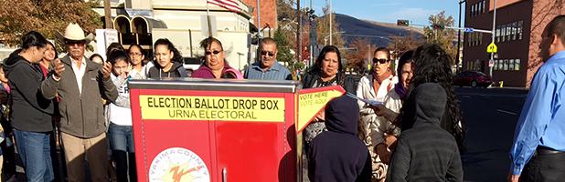 Photo of Latino voters standing around a ballot box in Yakima