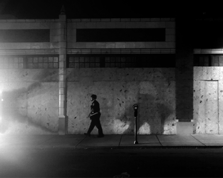 image of a police officer walking on a sidewalk