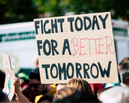 image of protestor holding sign that says fight today for a better tomorrow