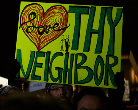 A photo of a man holding a sign that says love thy neighbor