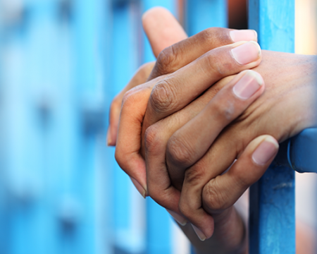Photo of a prisoner's hands through bars