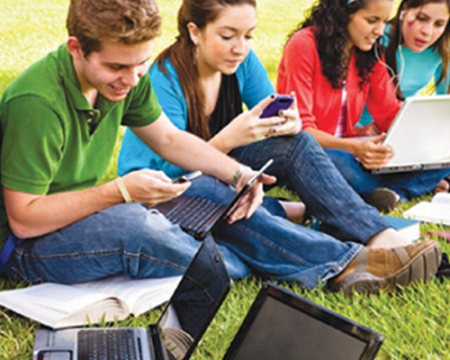 Photo of students using computers and mobile phones