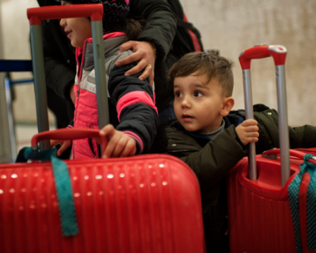 Photo of a small child with suitcases