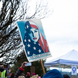 Photo of a sign picturing a Shepard Fairey illustration of a woman in an American flag hijab