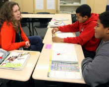 Photo of two students meeting with a teacher